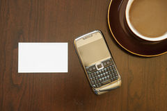 Cell phone 5175. Cell phone, blank business card and cup of coffee on brown table royalty free stock images