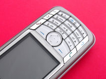 Cell phone. Closeup on bright red background Royalty Free Stock Photo