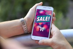 Cell phone with advertising sale on screen. Girl at balcony with smartphone a sale advertising on the screen. Cell phone publicity. Ecommerce, internet stock image