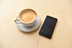 Cell Phone And Coffee Cup On A Vintage Table Stock Photo