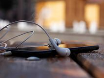Free Cell Phone And Headphones Left On The Bench Royalty Free Stock Photo - 159775995