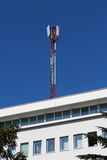 Cell phone antenna tower on top of white office building Royalty Free Stock Photography