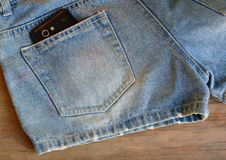 Cell phone in back pocket of short blue jean pant on wooden board Stock Photos