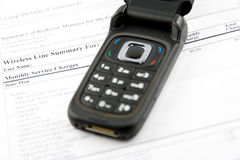Cell phone bill. A cell phone laying on the statement Royalty Free Stock Images
