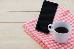 Cell phone and black coffee on table cloth on wooden,high angle view Royalty Free Stock Photos