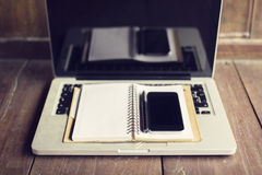 Cell phone, blank diary and laptop on a table Royalty Free Stock Images