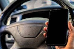 Cell phone with blank screen. In hand on car steering wheel background. Black screen of phone for your inscription or pictures Royalty Free Stock Photo