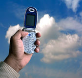 Cell phone and blue sky. Photo of hand holding a cell phone up towards the blue sky royalty free stock images