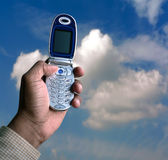 Cell phone and blue sky. Photo of hand holding a cell phone up towards the blue sky. Note: This file is to replace the approved file (1191039 royalty free stock image