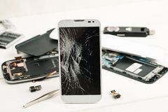 Cell phone with broken display among disassembled gadgets.  stock photos