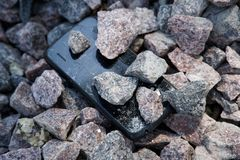 Cell phone with broken glass on gravel granite stones, unbreakable gadget.  royalty free stock images