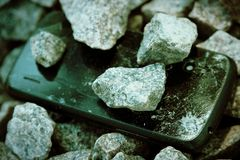 Cell phone with broken glass on gravel granite stones, unbreakable gadget.  royalty free stock image