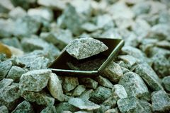 Cell phone with broken glass on gravel granite stones, unbreakable gadget.  royalty free stock photography