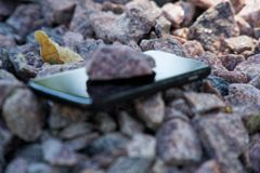 Cell phone with broken glass on gravel granite stones, unbreakable gadget.  royalty free stock photo