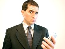 Cell Phone Businessman. Businessman holding a cell phone and raising an eyebrow royalty free stock photos