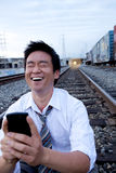 Cell Phone Call on Train Tracks. An Asian man sitting on the train tracks making a call Stock Photo