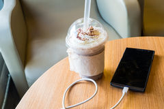 Cell phone charging in the cafe with a plastic cup of iced chocolate frappe Royalty Free Stock Images