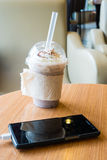 Cell phone charging in the cafe with a plastic cup of iced chocolate frappe Royalty Free Stock Image