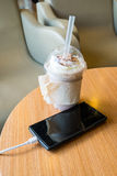 Cell phone charging in the cafe with a plastic cup of iced chocolate frappe Royalty Free Stock Photography