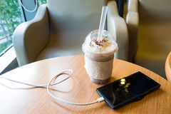 Cell phone charging in the cafe with a plastic cup of iced chocolate frappe stock photo