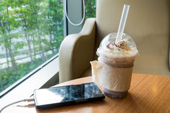 Cell phone charging in the cafe with a plastic cup of iced chocolate frappe royalty free stock photo