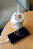 Cell phone charging in the cafe with a plastic cup of iced chocolate frappe stock photography