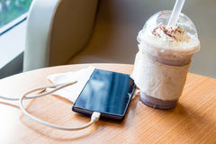 Cell phone charging in the cafe with a plastic cup of iced chocolate frappe Stock Image