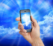 Cell Phone Christian Cross. A hand holding a cell phone with a cross and sky on the screen Stock Photography