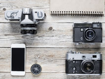 Cell phone, compass and vintage cameras. On wooden table royalty free stock photos
