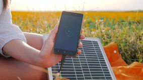 Cell phone connected to solar photovoltaic panels outdoor, battery charger solar powered, renewable energy, close up. Screen cellular telephone, hands girl stock video
