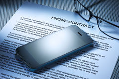 Cell Phone Contract. A cell phone resting on a phone contract Stock Images