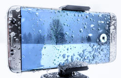 Cell Phone Covered in Ice & Water Drops. Cell phone covered in ice and water being used to shoot video in a cold snow storm royalty free stock image