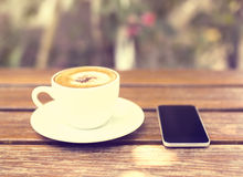 Cell phone and cup of coffee on a wooden table Stock Images