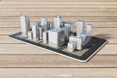 Cell phone with 3D city buildings on a wooden table, navigation Royalty Free Stock Image