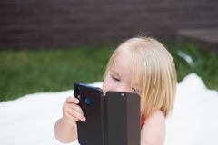 Cell phone dependency. Small child make phone call. Small girl use mobile phone. Girl child with blond hair talk on cell. Phone. New technology for children stock images