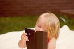Cell phone dependency. Small child make phone call. Small girl use mobile phone. Girl child with blond hair talk on cell. Phone. New technology for children stock image