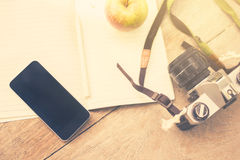 Cell phone, diary, old camera and apple Royalty Free Stock Photography