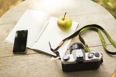 Cell phone, diary, old camera and green apple. Close up Stock Photos
