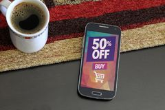 Cell phone with a 50% discount advertising on screen. Smartphone with a 50% discount advertising on the screen. Beside a cup of coffee. Marketing, ecommerce stock image