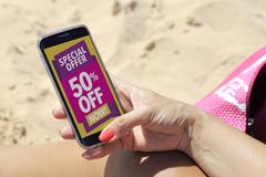 Cell phone with a 50% discount advertising. Young woman resting on the beach in the sun with a smartphone where she reads 50% off advertising on the screen stock image