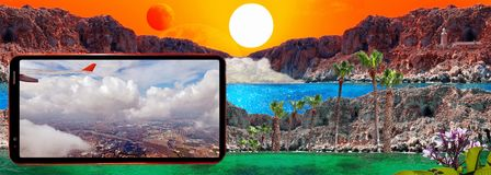 Cell phone displaying aircraft wing and cloudy sky on background of fantastic landscape with sun, red moon, rocks, light house,. Concept of traveling and royalty free stock photo