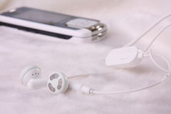 Cell phone and ear buds Stock Photos