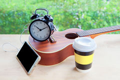 Cell phone with earphone, alarm clock, ukulele guitar and coffee Royalty Free Stock Image