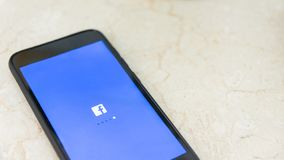 Cell phone with facebook app opening, showing logo and loading screen stock images