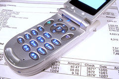 Cell Phone on Financial Bank Statement for Inquiry. Open and lit clam shell flip style cell phone over bank statement for calling inquiry Stock Photography