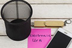 Cell phone and flash drive near trash can with the words: Electronic Urn.  royalty free stock photography