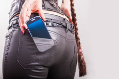 Cell phone in girl's back pocket. Close up of a cell phone in girl's back pocket royalty free stock photo