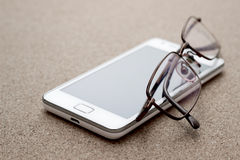 Cell phone and glasses Royalty Free Stock Photography