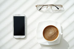 Cell phone, glasses and cup of coffee Stock Photo