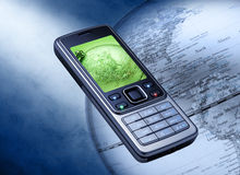 Cell Phone Global Communication. A cell phone over a world globe Royalty Free Stock Photos